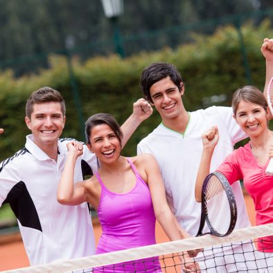 Excited group of tennis players with arms up